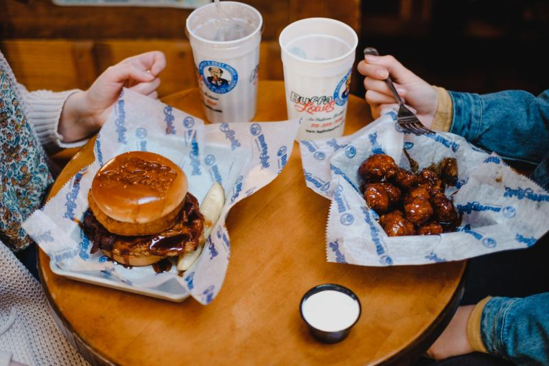 Visitors enjoy a burger and wings from Bloomington's famous BuffaLouie's restaurant.