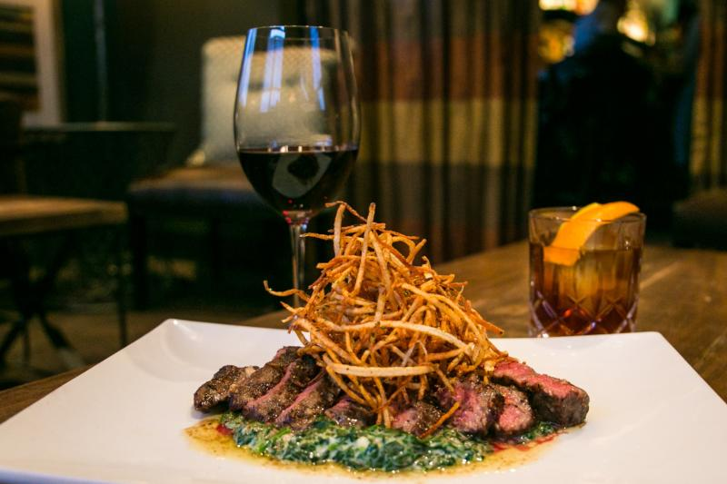 A glass of wine, a cocktail, and a steak dish from C3