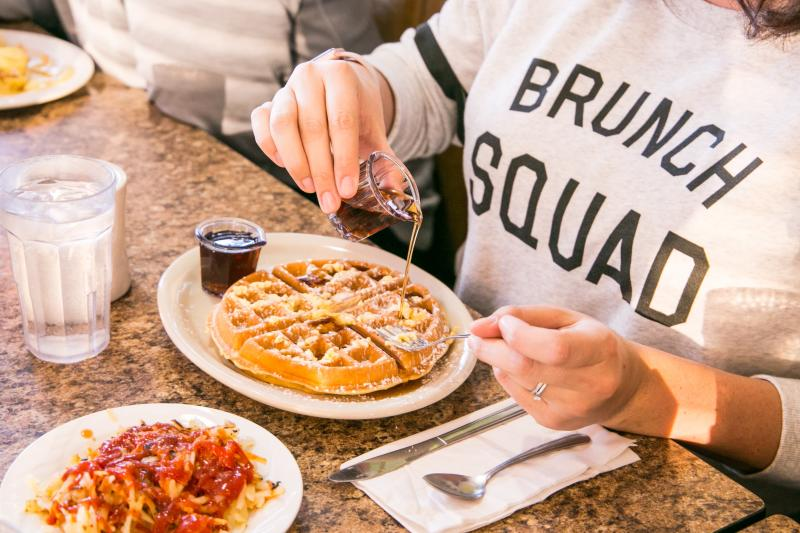 Woman pouring maple syrup on a homemade waffle at Cozy Table