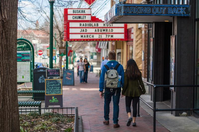 A couple walking hand-in-hand down Kirkwood Avenue