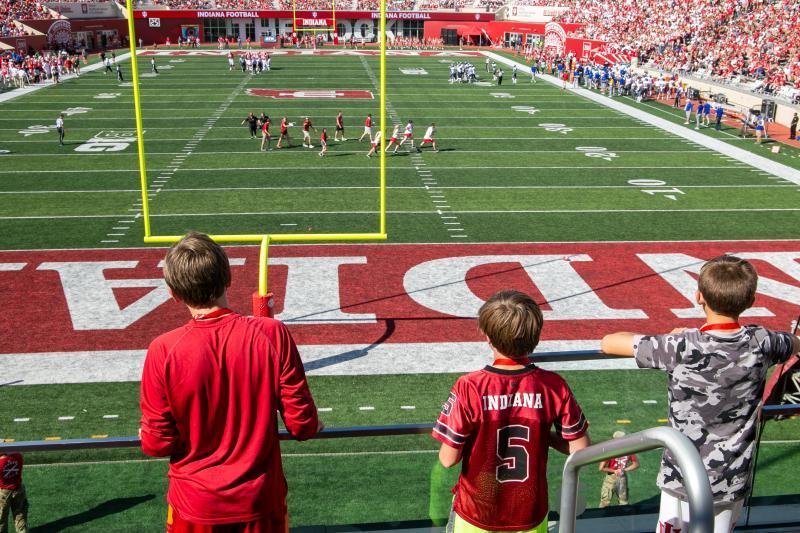 Three boys watching an IU football game at Memorial Stadium