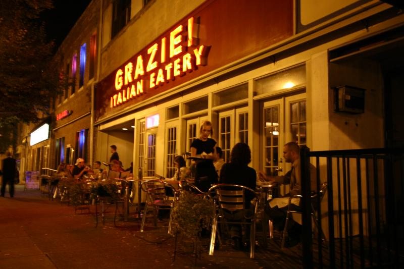 Visitors enjoy outdoor dining in front of Grazie Italiano's patio at night