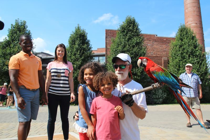 A bird keeper and his parrot pose for a photo with two little girls at the Bloomington Community Farmers' Market