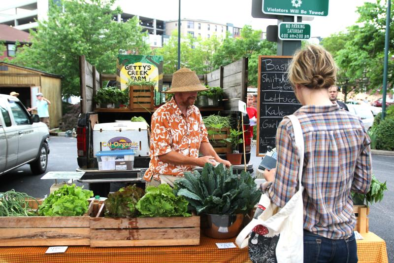 Woman purchasing produce from the Gettys Creek Farm vendor at the Bloomington Community Farmers' Market