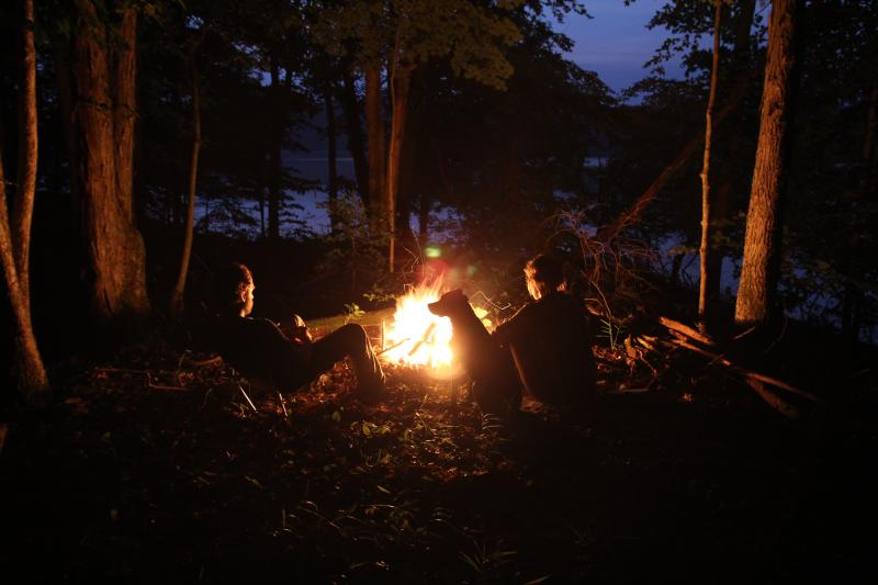 Couple with their dog sitting around a camp fire while camping in Bloomington Indiana
