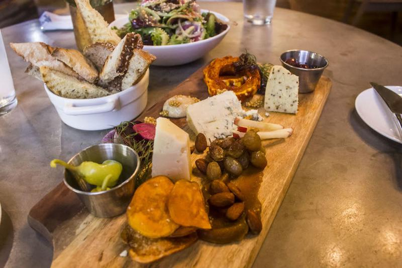A charcuterie board, bread basket, and salad from Feast
