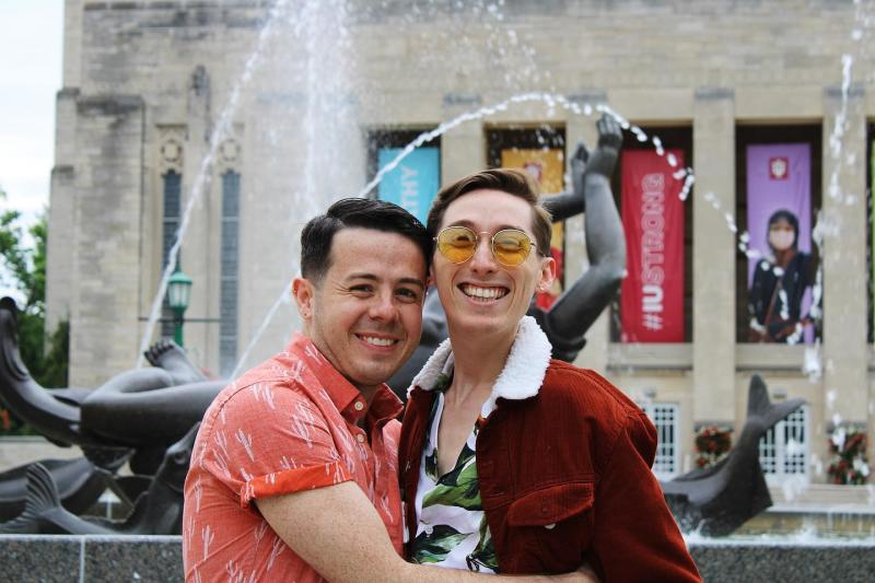 A gay couple smiling for a photo at Showalter Fountain