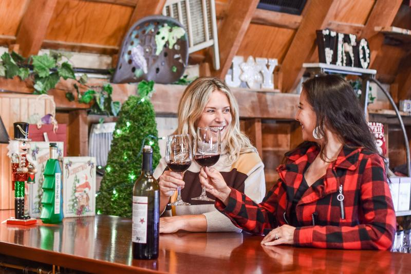 Women cheers wine glasses at Huber's during the holidays