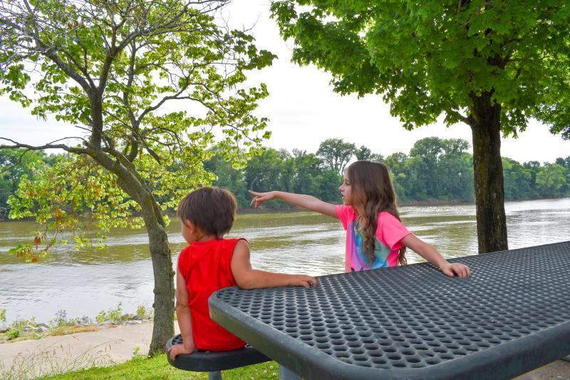 kids at a picnic table by a river