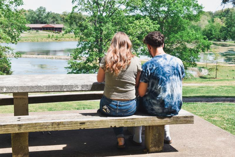 a young couple at a picnic table near a lake