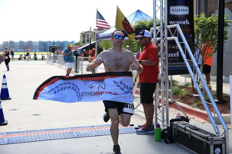 Shirtless man crossing the finish line at the Irving Marathon