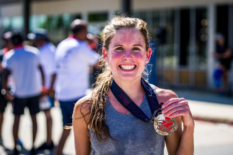 Smiling woman with medal at the Irving Marathon
