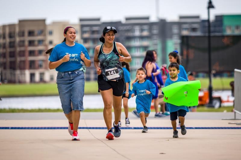 Two women and children running at the Irving Marathon