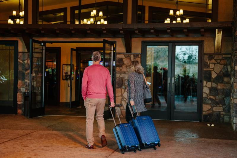 A couple with matching blue luggage enters the lobby at Three Rivers Casino