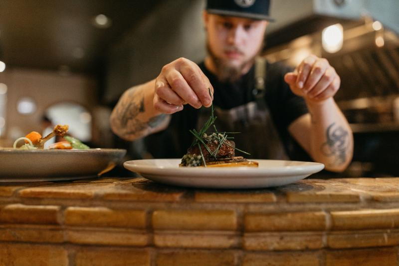 Chef puts finishing garnishes on a dish at Marche.