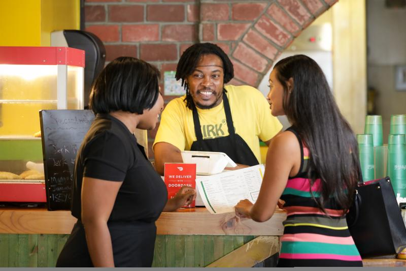 Two women ordering food at Kirk's Jerk Chicken