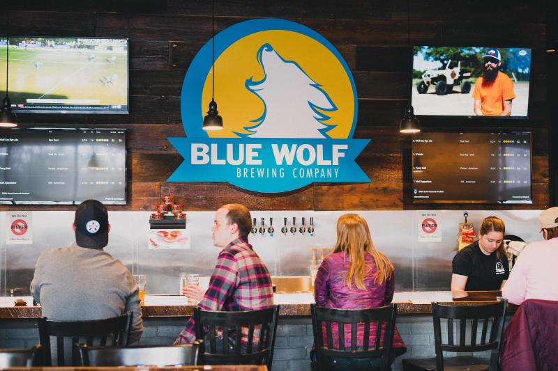 Patrons seated at the bar inside of the Blue Wolf Brewing Co