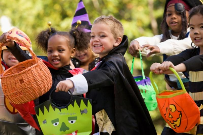 A group of children trick-or-treating with a young boy dressed as a vampire holding a Frankenstein-shaped bag in front of a girl dressed as a ladybug