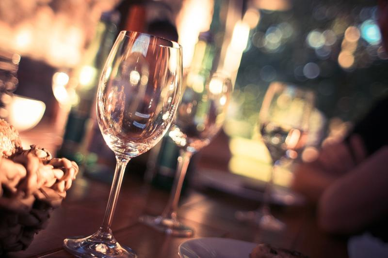 Two Wine Glasses sit on a bar with an out-of-focus background
