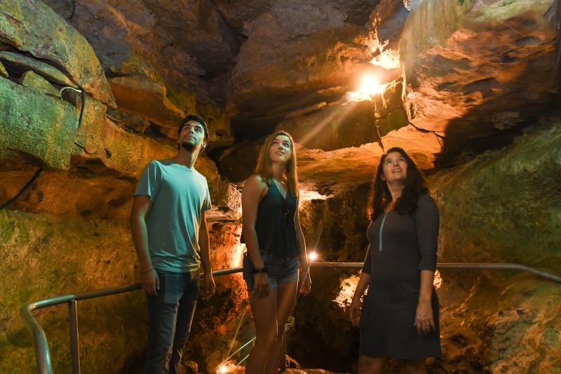 Family gaze at the rock formations in Wonder World Cave in San Marcos, Texas
