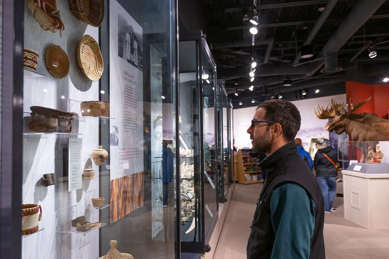 a man looks at a museum display of Alaska Native artifacts