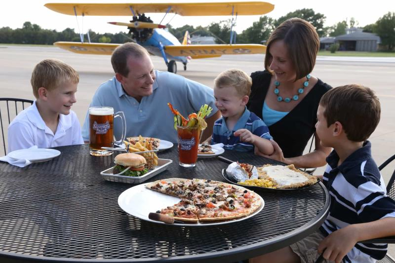 A family enjoys burgers and pizza on the patio at Stearman Field while a small prop plane is parked on the landing strip behind them