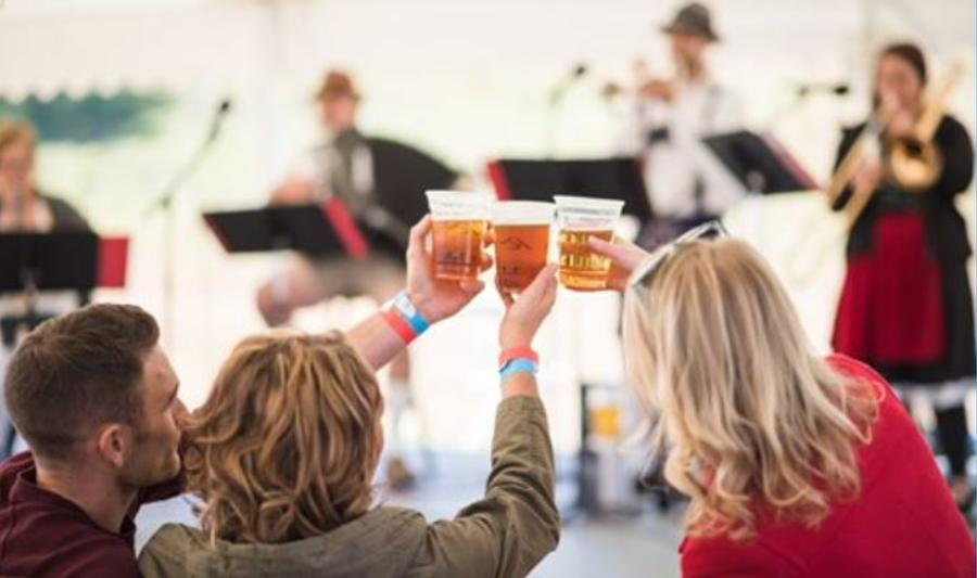Three people cheers plastic cups full of beer during a live musical performance.