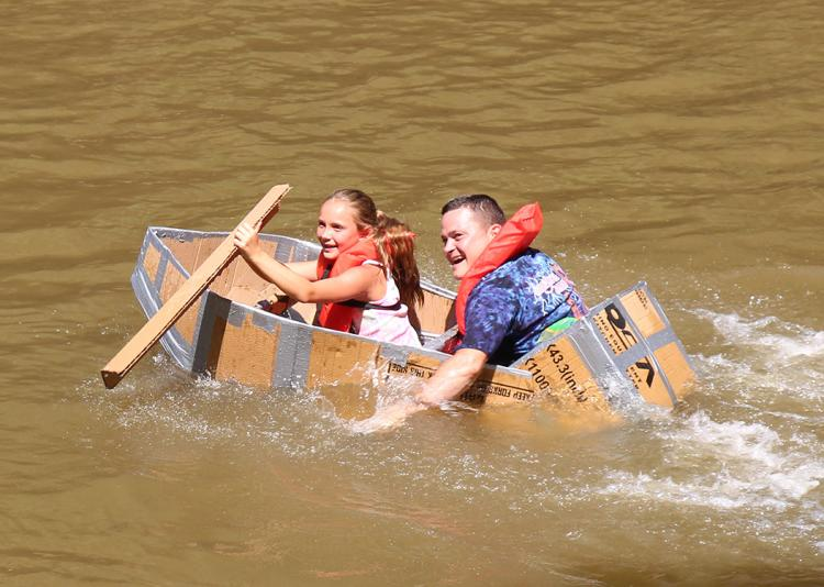 Two people paddling a handmade cardboard boat in the Neuse River for the Smithfield River Rat Regatta.