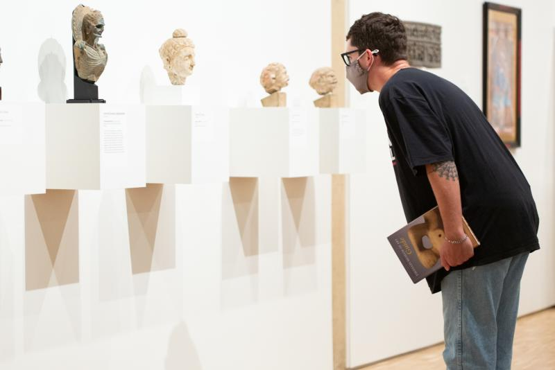 A visitor studies the collections of ancient busts at Eskenazi Museum of Art