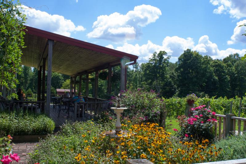 Butler Winery's outdoor patio, surrounded by wildflowers and lush greenery