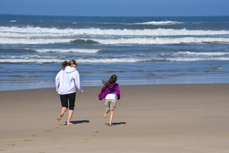 A woman and young girl run towards the waves on the beach.