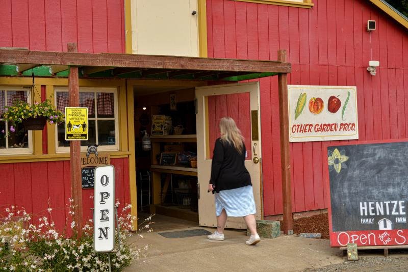 Woman wearing a dress and a shawl enters the red barn market at Hentze Family Farm