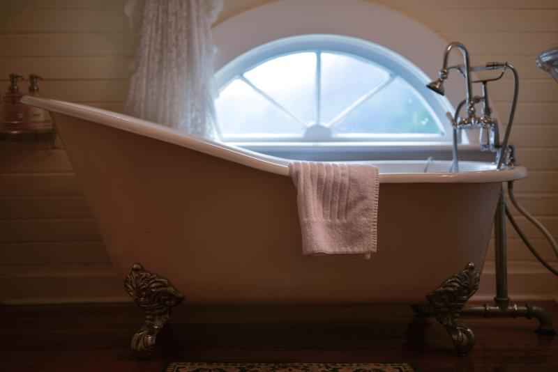 An antique claw foot tub with a white towel draped over the side sits in front of a small foggy window at the Heceta Head Lighthouse Bed & Breakfast.
