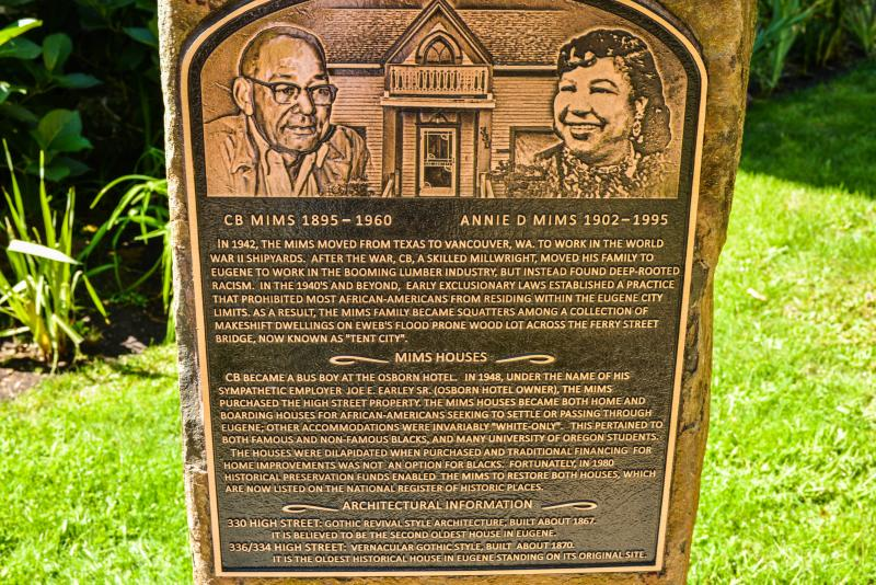 A historic marker with a relief sketch at the top gives the history of the Mims House and the Black family that lived there during Eugene's period as a sundown town.
