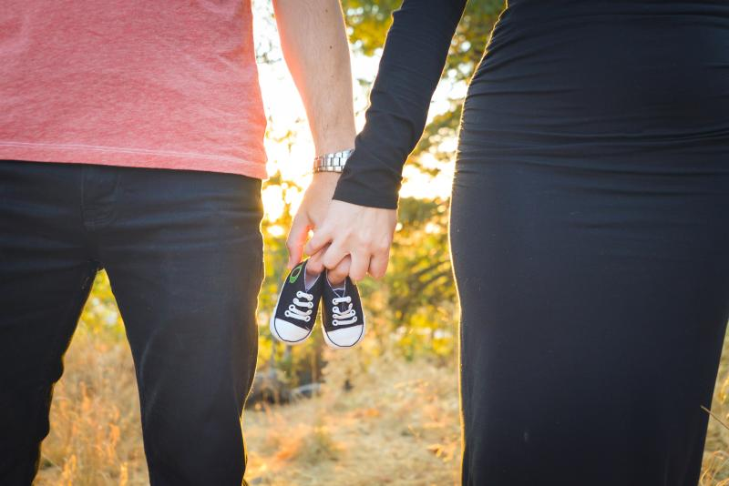 Couple stands side-by-side holding a pair of baby shoes between them with fall foliage in the background