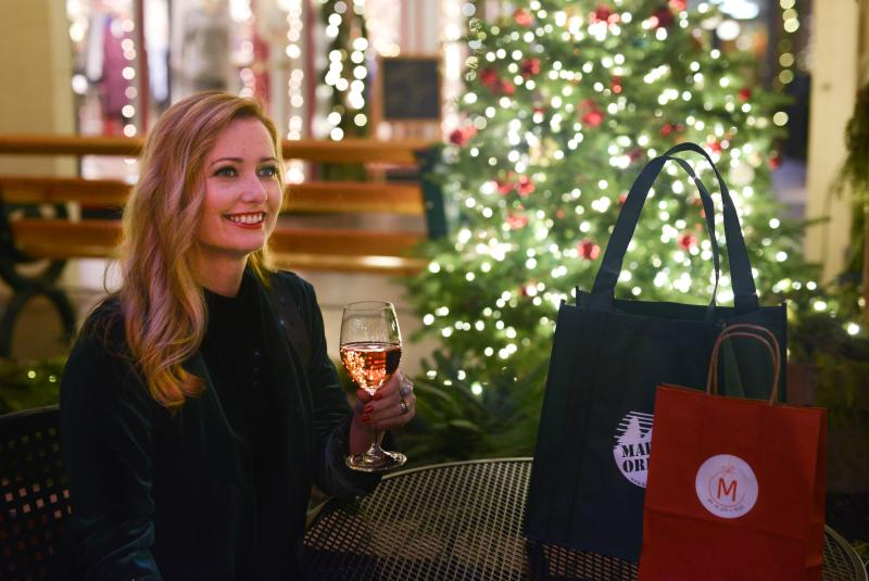 Woman with Christmas tree, wine and shopping bags.
