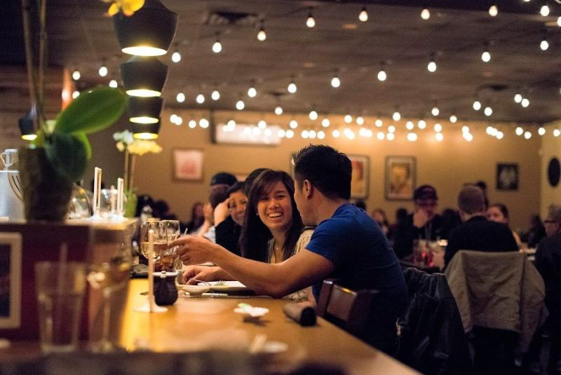 A couple sits at the bar enjoying a meal and drinks at Lemon Grass Thai
