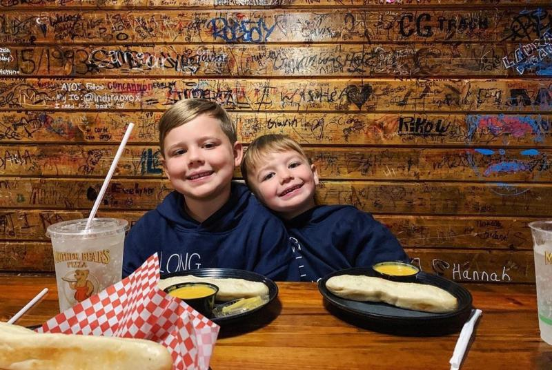 Two little boys smiling in a booth at Mother Bear's
