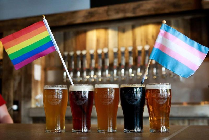 Five beers lined up with the Pride and Transgender flags for Pride Month