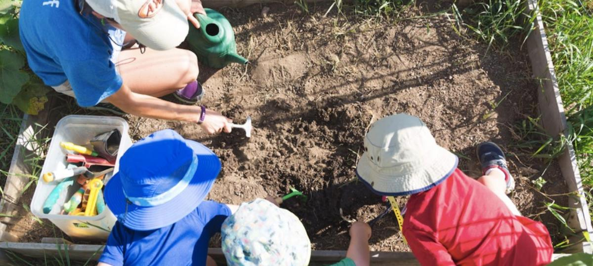 Kids digging in the dirt at Growing Gardens in Boulder
