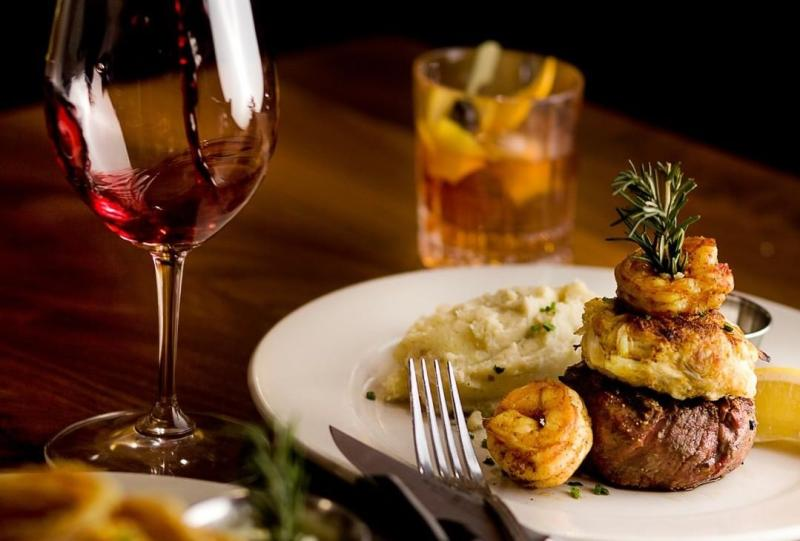 A surf n turf dish, a cocktail, and a glass of red wine from Uptown Cafe