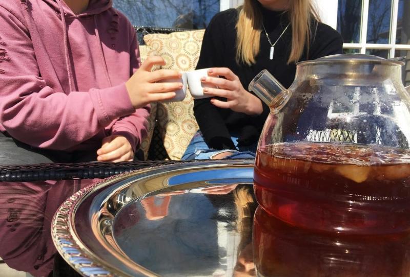 Two people cheers-ing their tea cups at BloomingTea