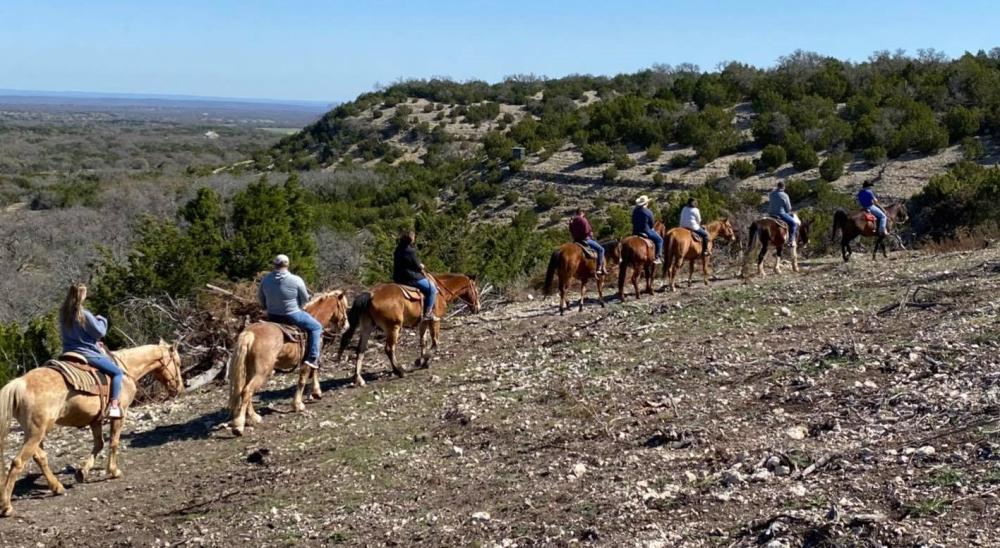 Horseback riders proceed single file along a trail at GF Ranch Trail Rides in Fredericksburg, TX