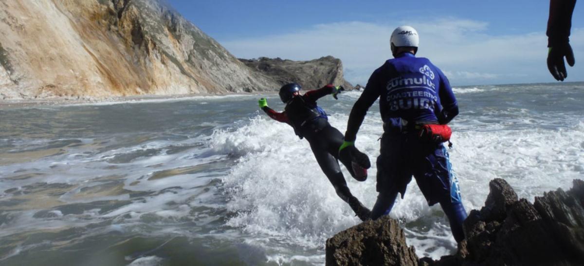 People jumping off rocks, coasteering
