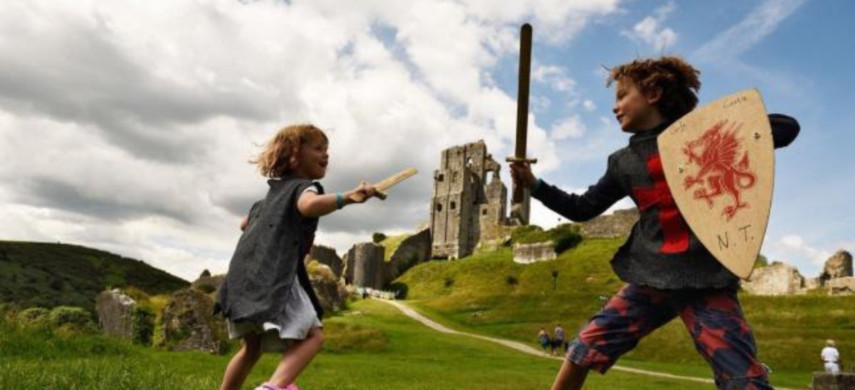Two kids playing with swords in front of Corfe Castle