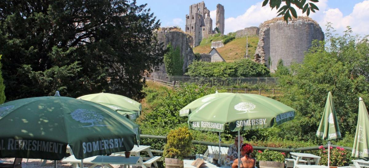 Outside tables at Greyhound Inn with Corfe Castle in the background