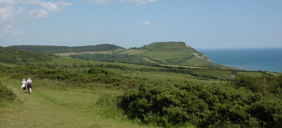 Two people walking at Stonebarrow, with a view of the Dorset coast in the distance