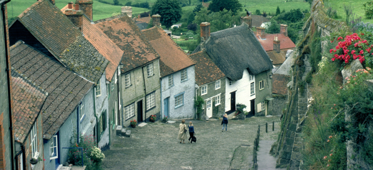 Three people walking down Gold Hill in Shaftesbury, Dorset