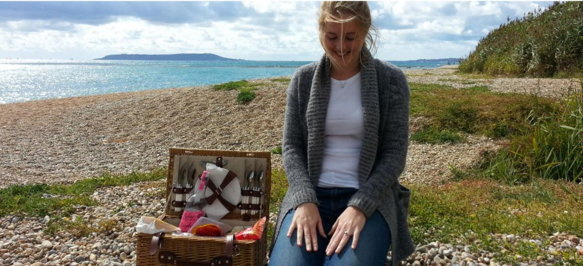 Woman showing engagement ring after being proposed to at Ringstead Beach, Dorset
