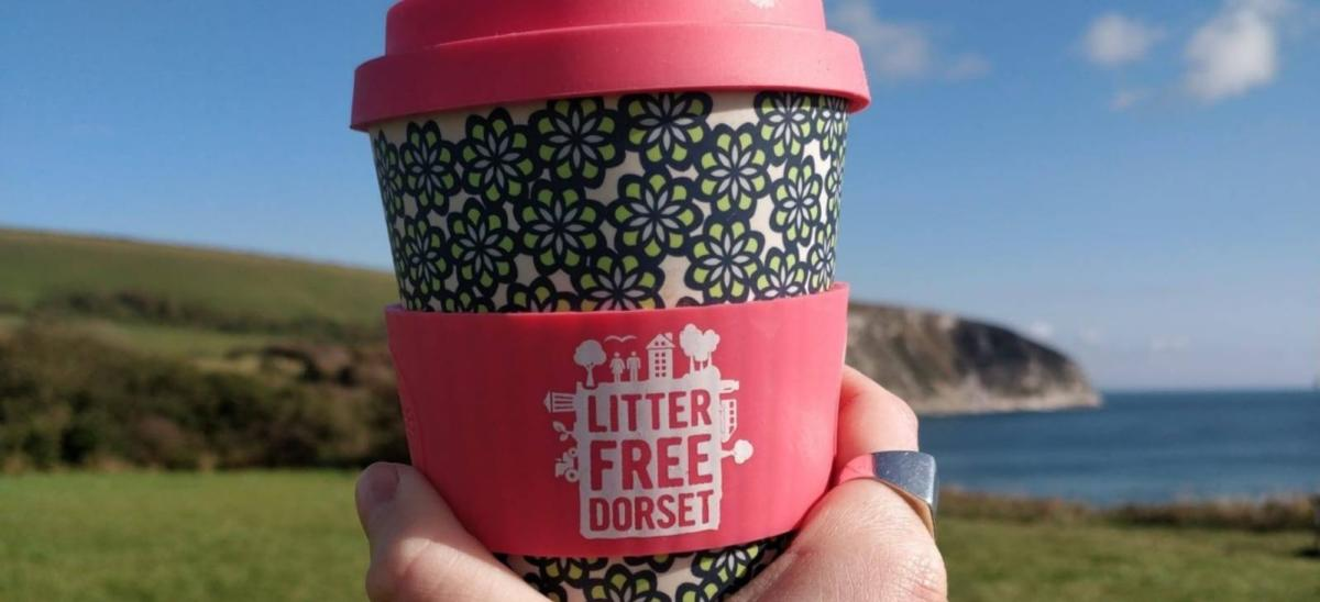 A person holding a Litter Free Dorset reusable coffee cup